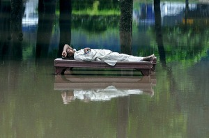 Man laying on a bench in a flooded park